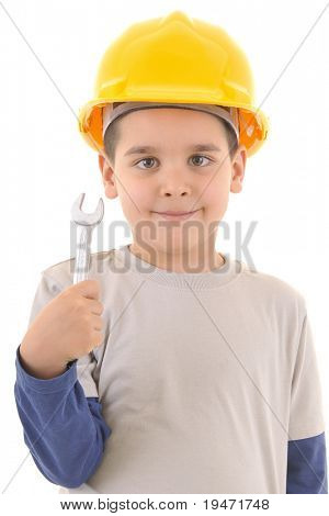 Little kid as a construction worker wearing yellow helmet with a 17 inch wrench in his hand. White background vertical studio picture.