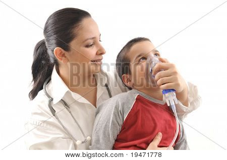 Happy female medical doctor with stethoscope applying oxygen treatment on a little boy with asthma. White background studio picture.