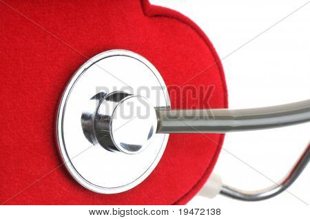 White background horizontal close up studio image of monitoring heart concept with stethoscope and red heart