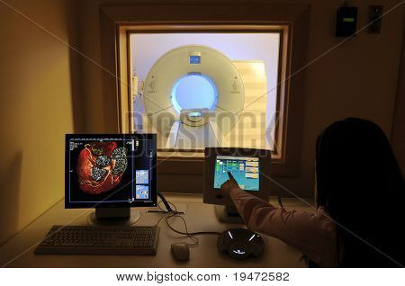 Magnetic Resonance Imaging machine from control room and a nurse showing results -a series of MRI.