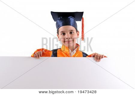 Elementary boy wearing graduation cap and gown holding a blank board