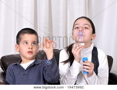 Teenage girl blowing soap bubbles her little brother catching.