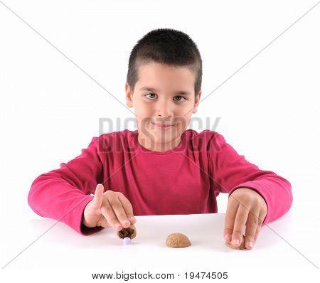 cute Boy traditionellen Shell-Spiel mit drei Walnuss-shells eine Reihe von Shell-Spiel-Bildern.