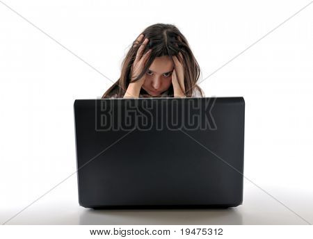 Teen girl frustrated behind a laptop isolated on white background - see more computer images.