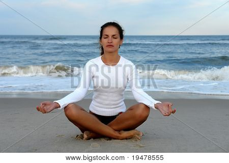 Young woman doing yoga on the ocean beach
