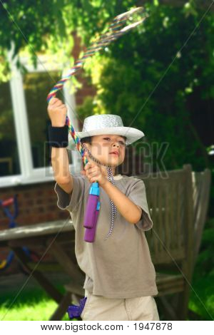 Young Boy As Cowboy With Skipping Rope Lassoo
