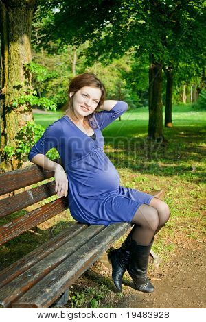 Beautiful pregnant woman resting in the park