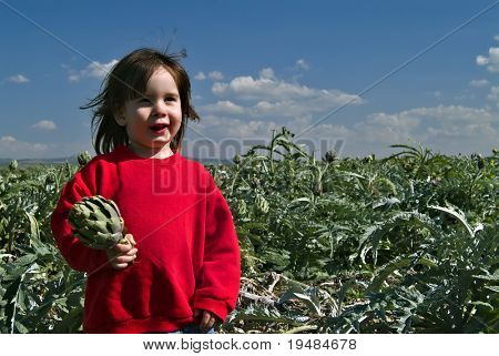 smiling young girl with red sweatshirt holding artichoke in an artichoke field