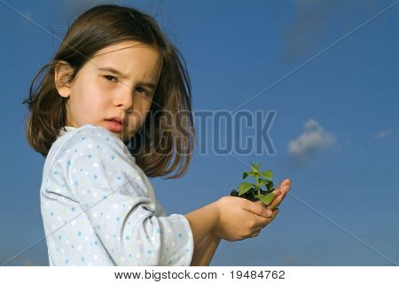girl holding plant against blue sky with a cloud