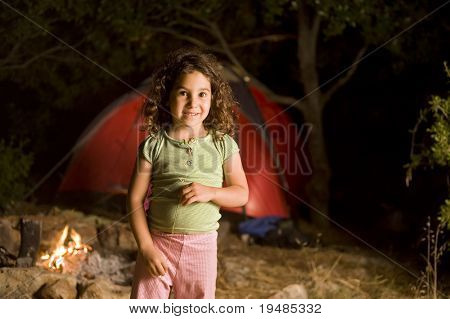 little girl at a camp at night in front of a red tent and a campfire