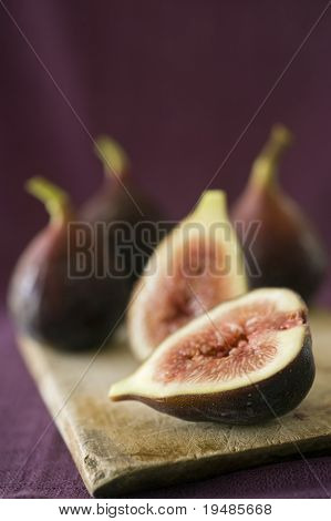 still life three whole figs and one sliced on a wooden cutting board