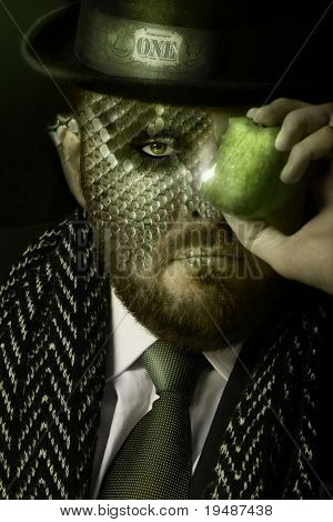 Portrait of reptilian man in expensive clothing holding a green apple