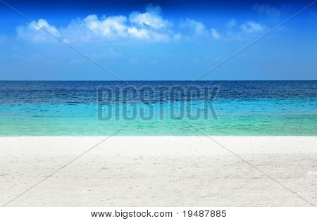 Caribbean beach featuring levels of white sand, emerald water, dark blue water, and blue sky with clouds