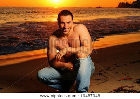 Casual shirtless good looking man on the beach at sunset in golden light