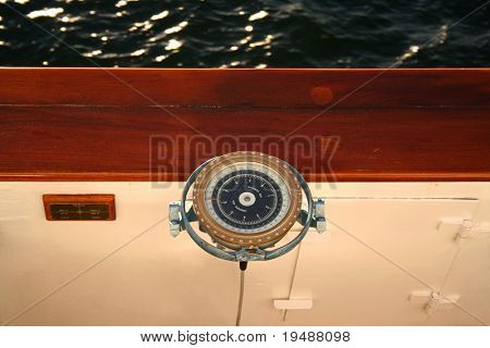 Modern compass onboard of the liner. Little bit shabby but beautiful. A close up. A geometrical composition. Behind a board of a wave in beams the sun.