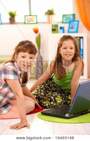 Elementary age girls sitting in living room with laptop computer, looking at camera, smiling.?