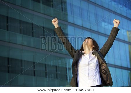 Young female professional stretching hands to celebrate business triumph, posing in front of blue glass facade of office building
