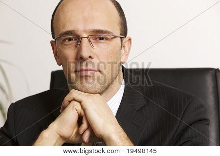 Businessman in suit sitting at desk in office, with gray background