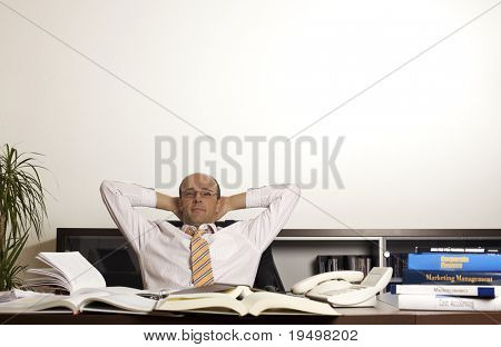 Businessman at office desk  leaning back in chair relaxing and being happy about work matters.