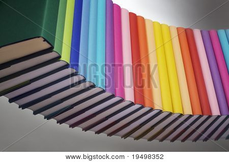 Curve alignment of in rainbow colors paper wrapped books with blank spine facing front, view from bottom-left, PHOTOGRAPH, NOT 3D RENDER.