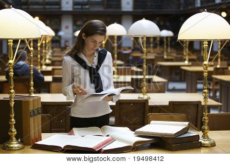 Young confident student standing at desk in old university library studying books.