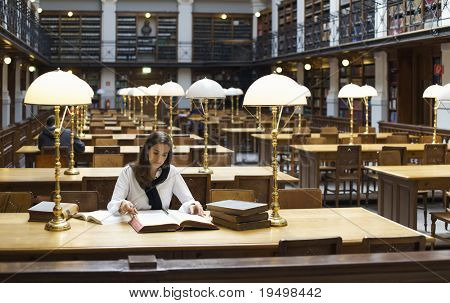 Attractive student sitting at desk in old university library studying books.