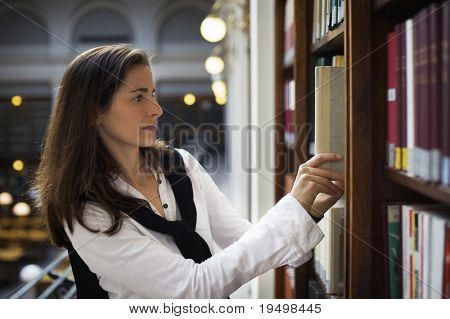 Young attractive woman standing at bookshelf in old university library searching for  books.