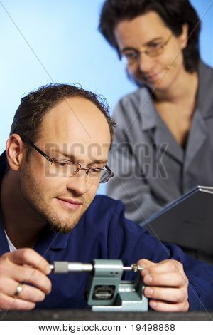 Close-up of young male engineer in blue overall taking precision measurement with screw micrometer of metal toothed wheel  and assistant in background watching him, isolated on blue background.