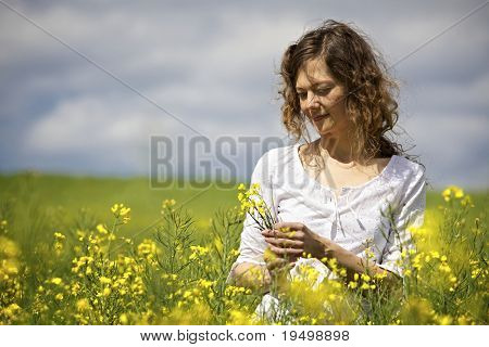 Content woman in white dress enjoying picking flowers in yellow rapeseed field.