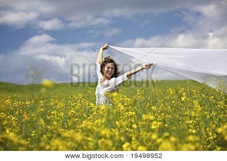 Joven feliz en el campo de colza amarillo sosteniendo un trozo largo blanco de tela en el viento.