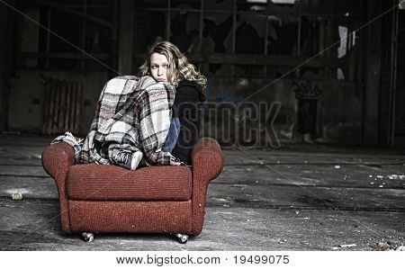 Sad girl sitting in shabby red sofa being covered with old blanket.