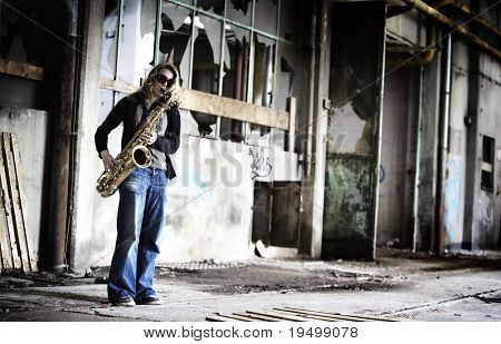 Groovy girl playing saxophone in run-down factory.