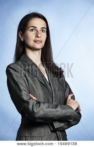 Half-body portrait of smiling confident businesswoman with entwined arms in grey suit looking up-right.