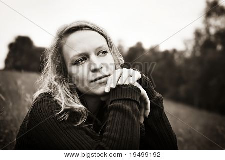Portrait of young woman sitting in meadow and reflecting on something, sepia toned.