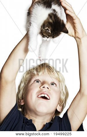 Handsome boy holding up sweet kitten and adoring it, isolated on white background.