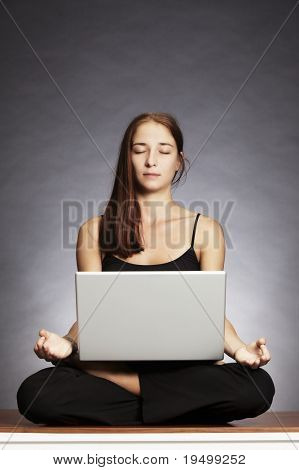 Balance in at work: Young pretty woman sitting in lotus posture on floor with laptop on her lap, backlit grey background.