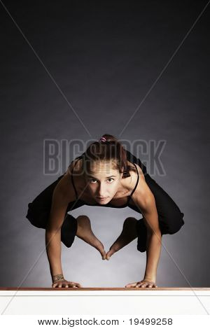 Young pretty woman in yoga crow posture (bakasana), backlit on grey background, front view.