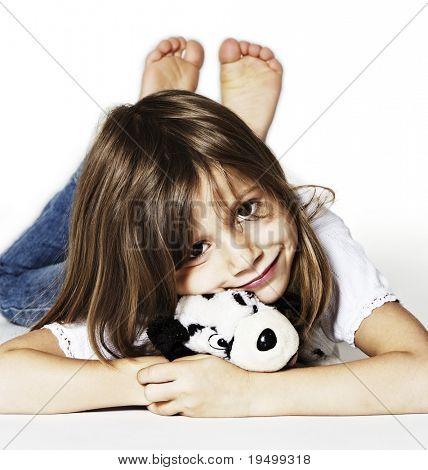 Inocentemente sonriente a niña con peluche, tendido en el suelo en estudio, aislado sobre fondo blanco.