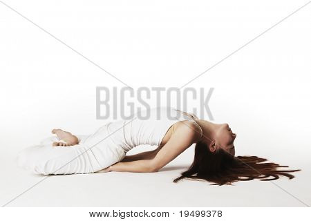 Young lady practicing yoga in lotus fish posture (Matsyasana) in white clothes with red hair spread out on white background, high-key image.