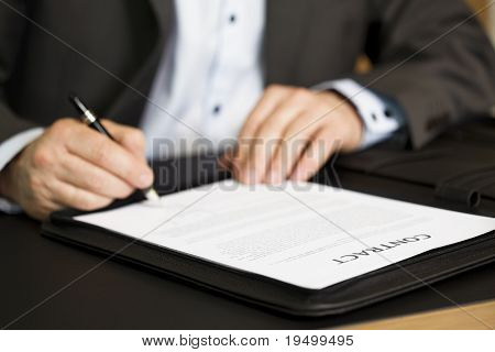 """Businessman in dark suit and blue shirt sitting in office at desk and signing a contract with shallow focus on word """"contract""""."""