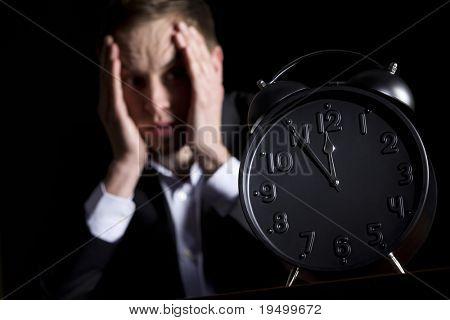 Pessoa de negócios no terno escuro, sentado na mesa de escritório com as mãos na cabeça, preocupou-se com de perto o