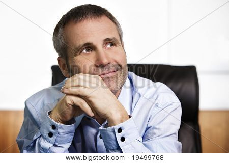 Close up portrait of smiling business manager in blue shirt sitting in office looking up and resting chin on  hands, thinking about positive business visions, isolated on white background.