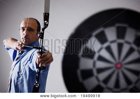Determined businessman aiming at target with bow and arrow, isolated on white background.