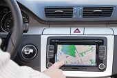 GPS navigation panel on dashboard inside a car. Finger pointing on destination point. poster