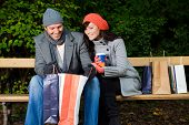 image of woman couple  - Pair of man and woman couple sitting on bank in park garden after shopping with bags - JPG