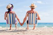 stock photo of couple sitting beach  - Relaxed summer vacation senior couple of old man and woman sitting on the beach - JPG