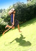 pic of jump rope  - Young girl skipping with her rope fast across the field on a lovely summer - JPG