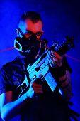 stock photo of skinheads  - Shot of a conceptual man in a respirator holding a gun - JPG