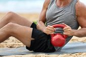 Fitness man lifting kettlebell weight training russian twist exercise. Exercising on beach training  poster