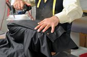 stock photo of tailoring  - Tailor ironing a jacket  - JPG
